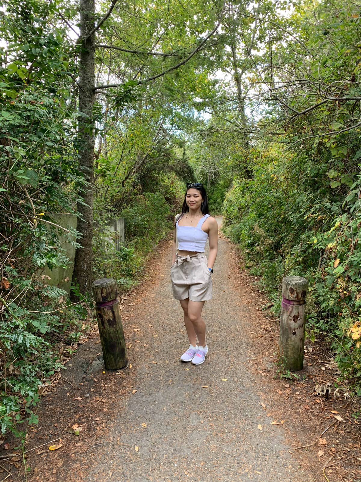 A woman with dark hair standing in the middle of a walking trail. Green shrubbery is visible on either side of her. She is wearing a white strapless top and natural coloured shorts, and has her hands in her pockets.