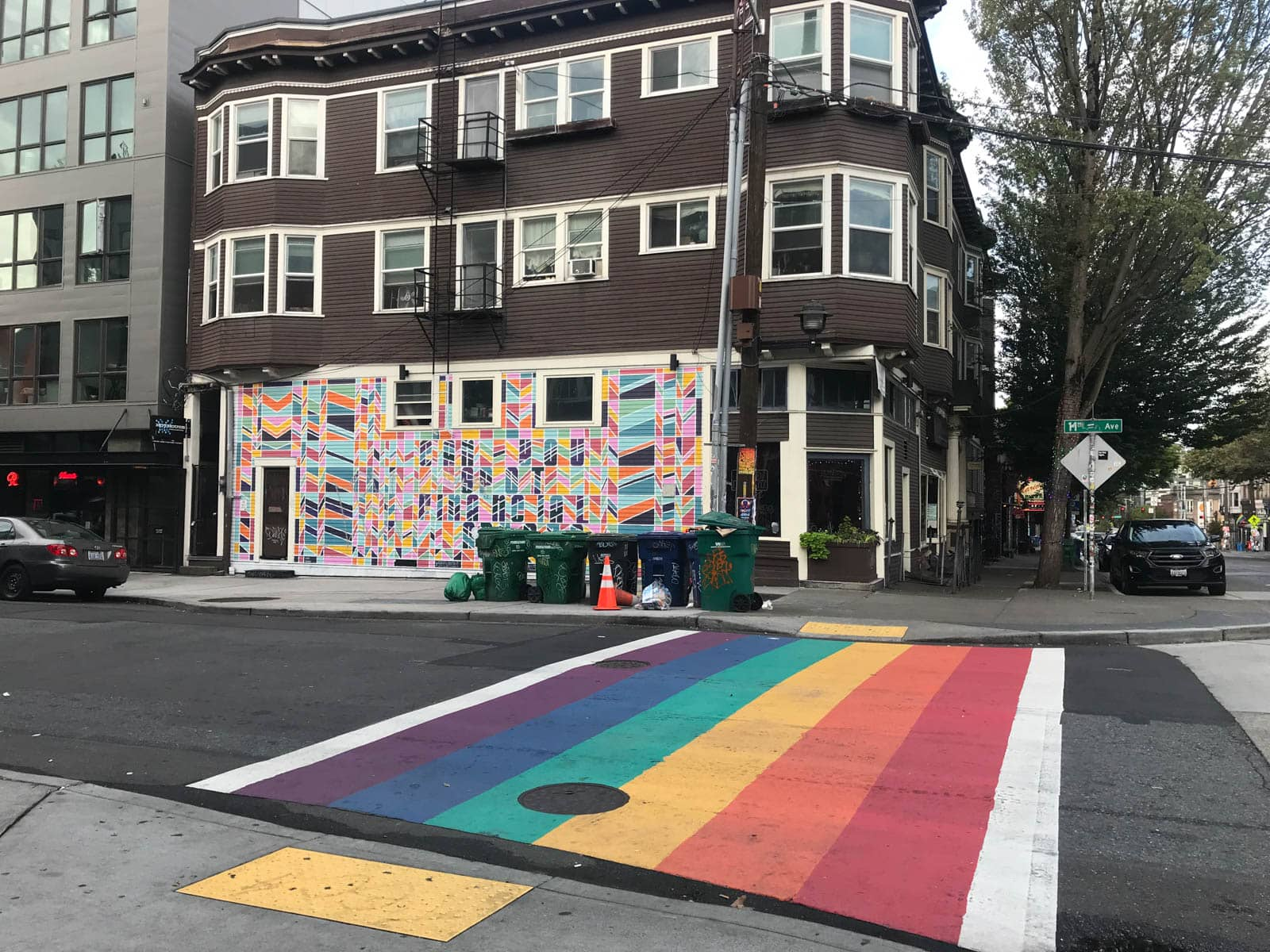 A rainbow-striped crosswalk painted on the road, with a colourful mural on the building on the opposite side of the road. The street is quiet.