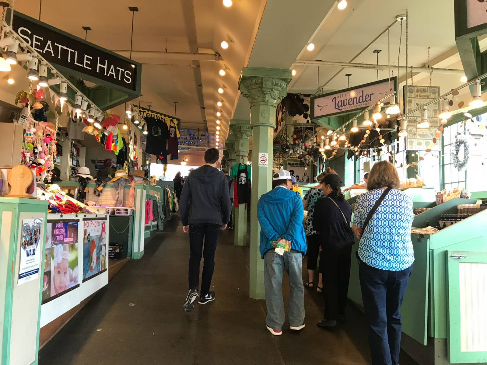 "Some people walking up a gradually sloping path between the stalls of an indoor market. One sign reads ""Seattle Hats"" and another reads ""Lavender""."