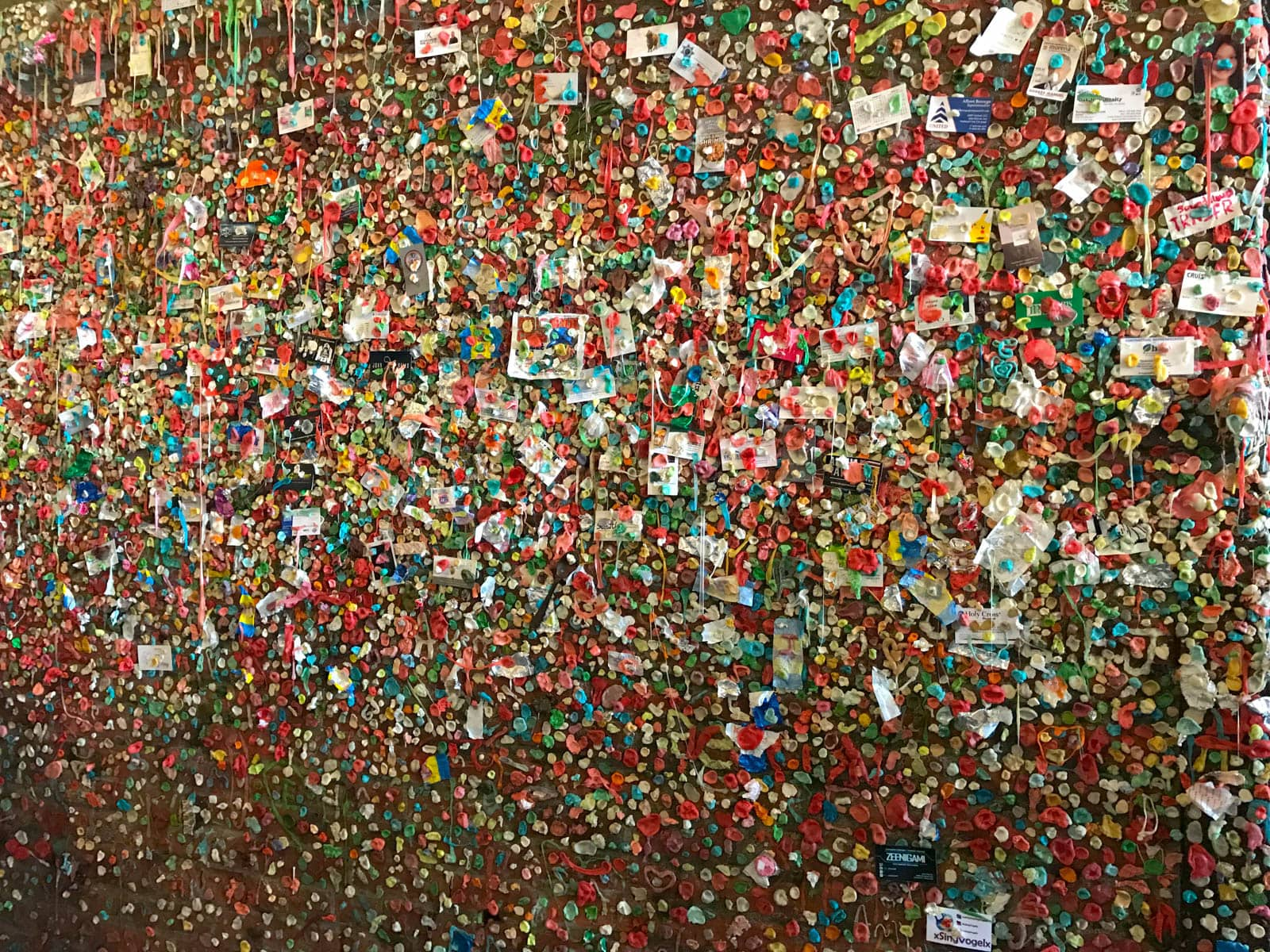 A brick wall littered with various pieces of paper, some resembling business cards and photographs, stuck to the wall with an infinite amount of small pieces of brightly coloured, masticated chewing gum.
