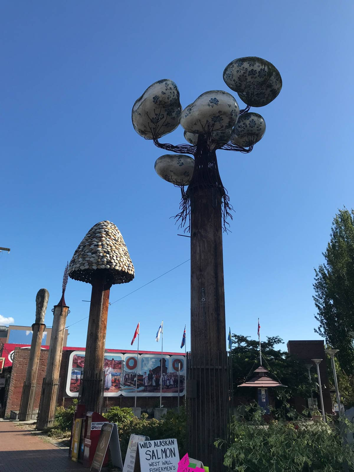 Some tall sculptures with mushroom tops, in the middle of an open park.