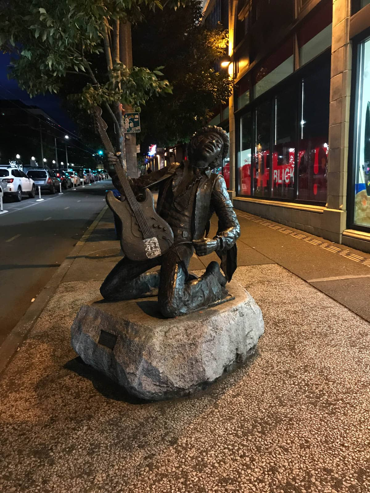 A dark bronze statue of a man playing a guitar, atop a stone with a plaque. The statue is on the sidewalk of a city, in the evening.
