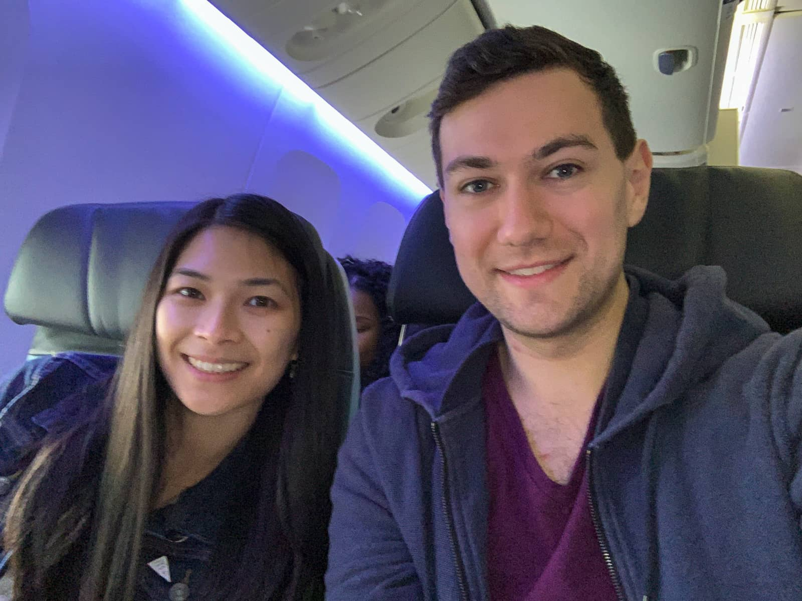 A selfie of a man and woman on a plane, smiling