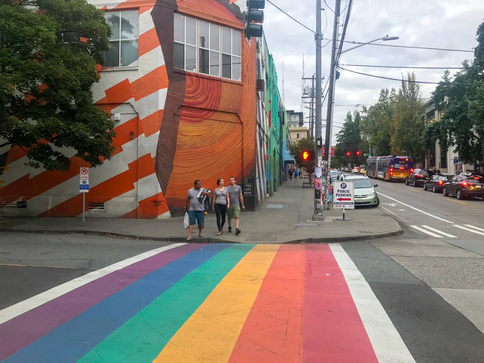 A pedestrian crossing painted in the colours of the rainbow. There are some pedestrians on the other side of the road waiting to cross, and the building behind them on the corner has a mural painted across its entire exterior