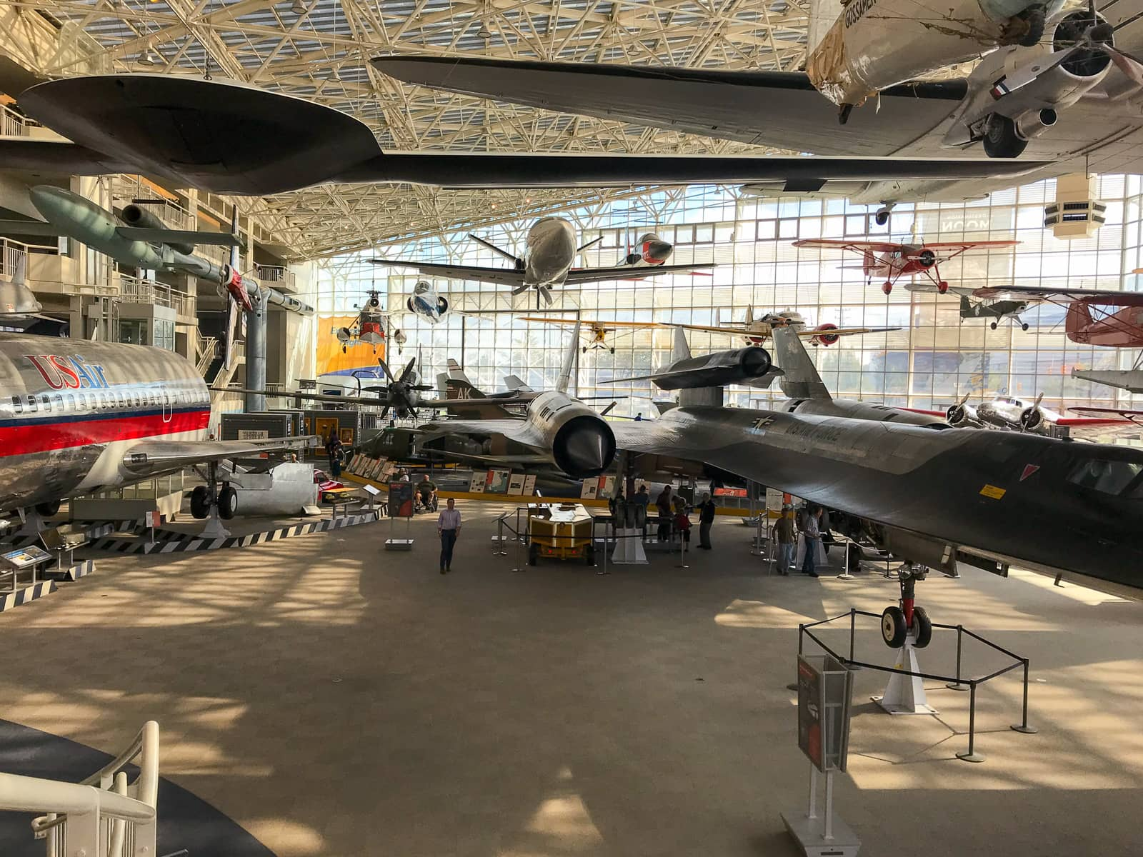 A big room with many lifesize models of airplanes on display, some hanging from the roof