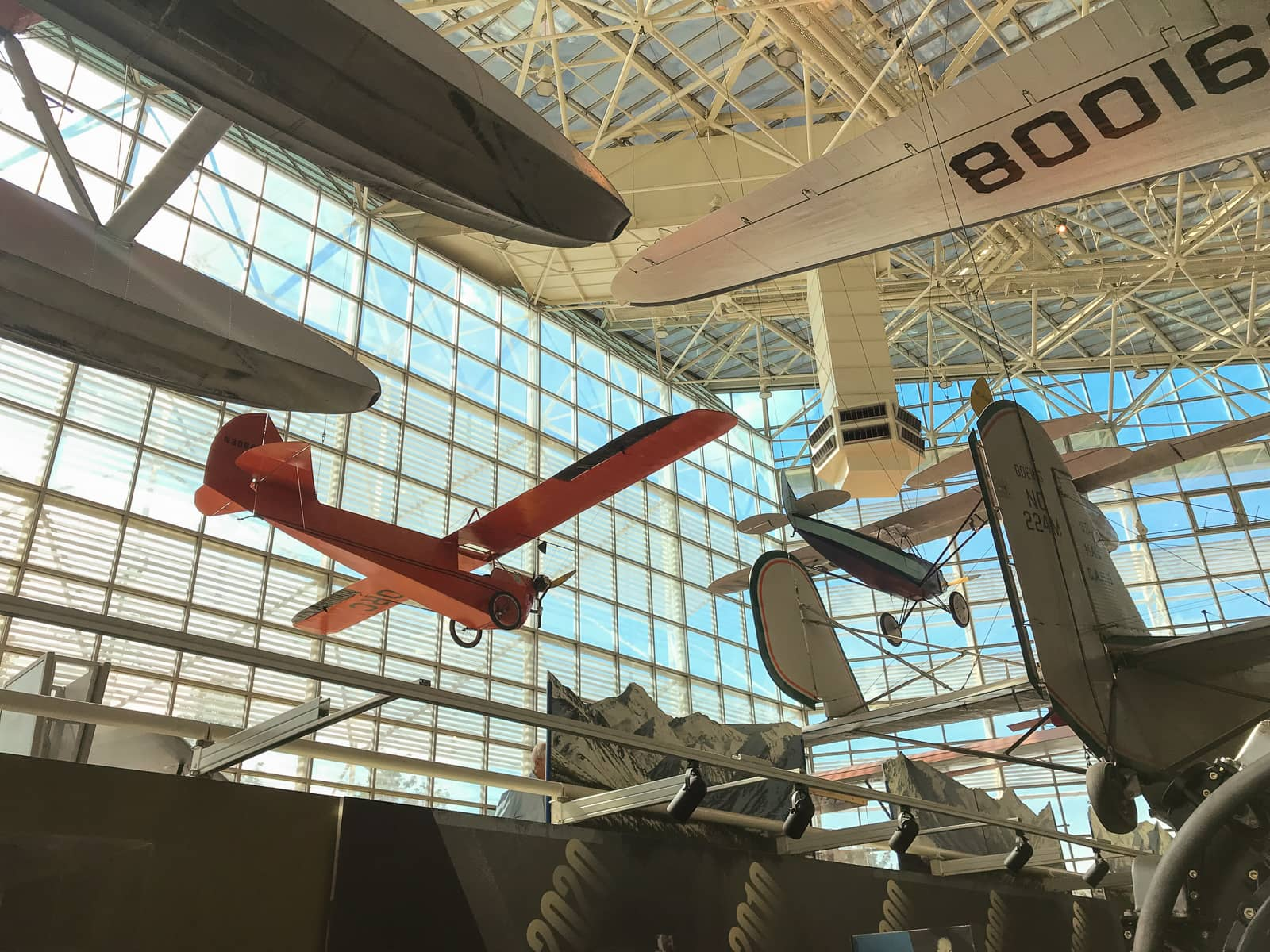 A view of the inside of the same building as previous photos, but looking outside the glass walls of the museum, with more planes being shown suspended from the ceiling