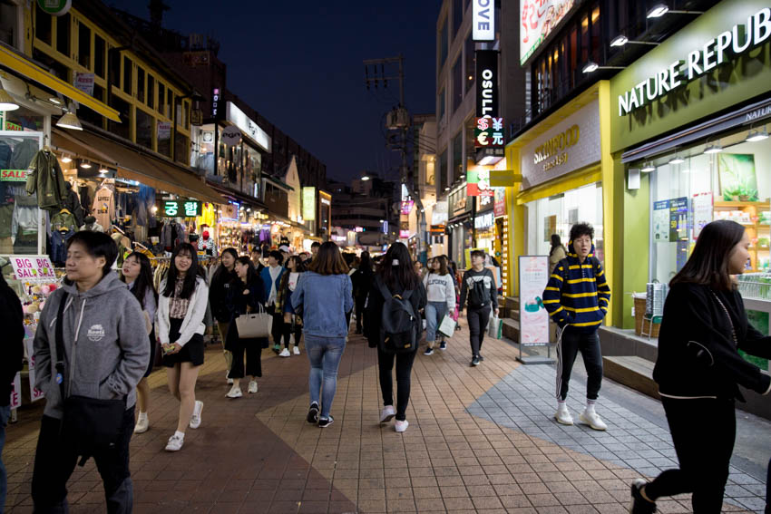 A view of the crowds down another street with fashion and skincare stores