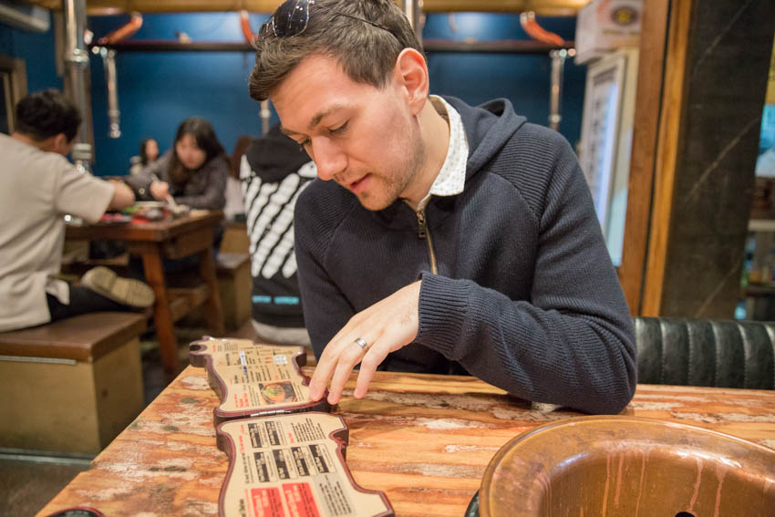 Nick perusing a cow-shaped menu at a barbecue restaurant