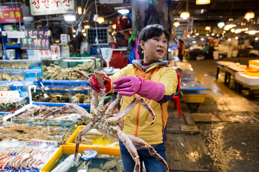 One of the vendors holding up a live crab