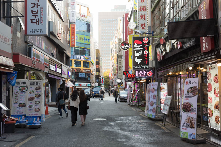 A street of eateries with their banners out front, advertising their products