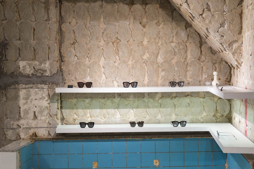 Front-on view of sunglasses with some old bath tiles visible