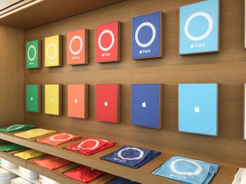 "A display of the designs of six different coloured shirts on a wooden background, all reading ""Apple Park"" with an Apple logo in place of the word ""Apple"""