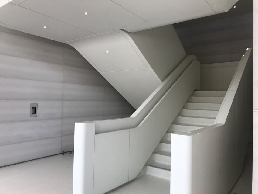 A staircase in white, with handrails built into the sides. The stairs change direction and there is no distinct pillar in the centre of the stairs.