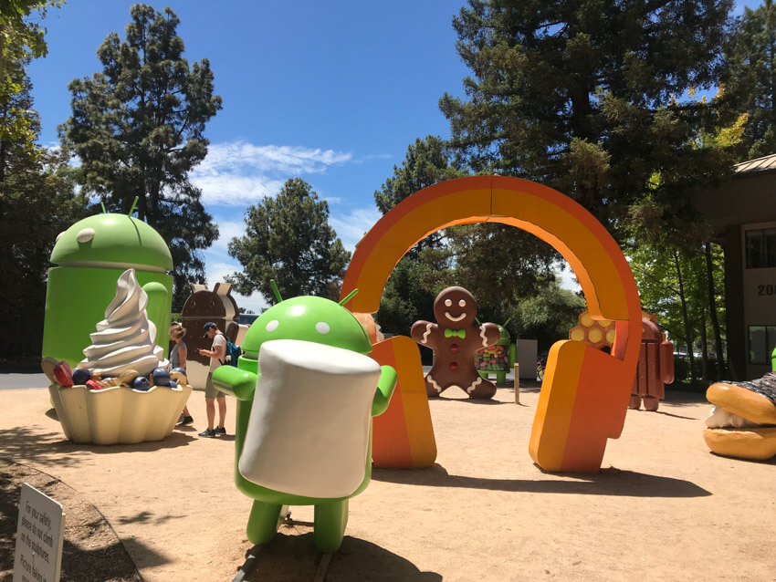 A dirt ground with various sculptures: a giant orange set of headphones; a frozen yoghurt with berries; the Google Android robot holding a marshmallow; as well as some others in the background