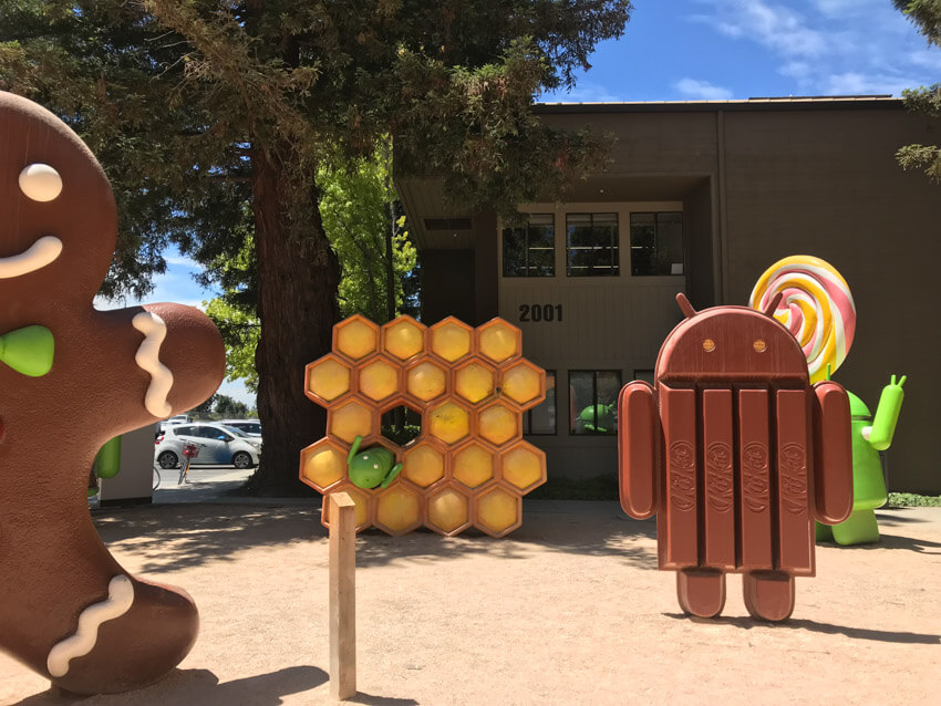 A dirt ground with various sculptures, a couple of metres tall. One resembles a robot made of chocolate Kit Kats, another resembles honeycomb, and another two can be partially seen: a green robot holding a lollipop, and a giant gingerbread man