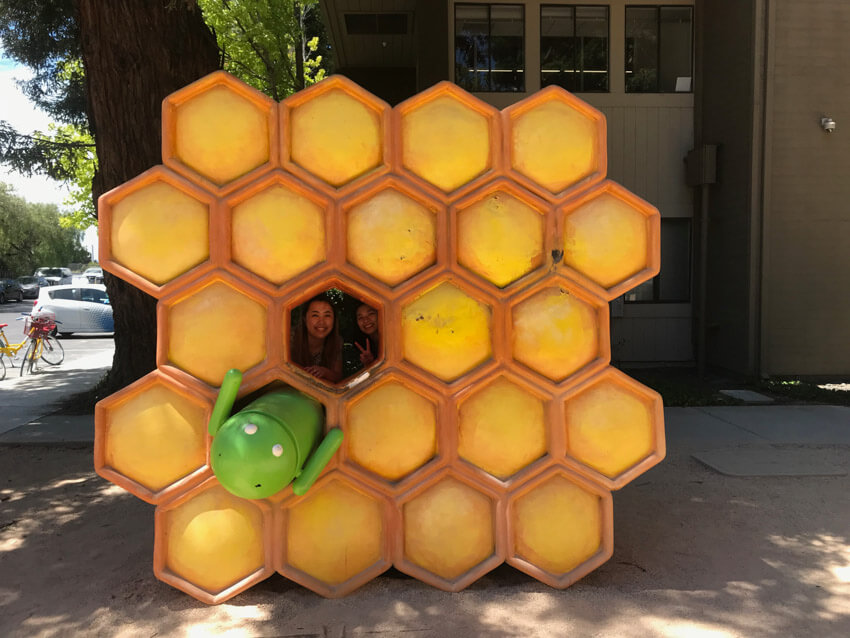 A sculpture resembling a honeycomb, with the Google Android robot in one honeycomb hexagon, and one hexagon free. Two women are looking through the free hexagon from behind and smiling