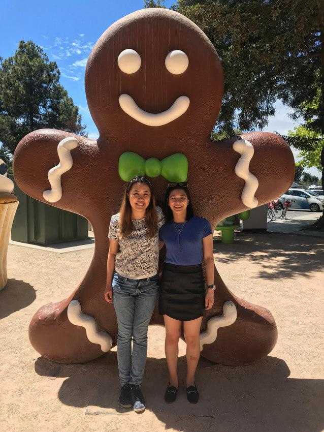 Two women smiling, with their arms around each other, and a giant brown gingerbread statue behind them