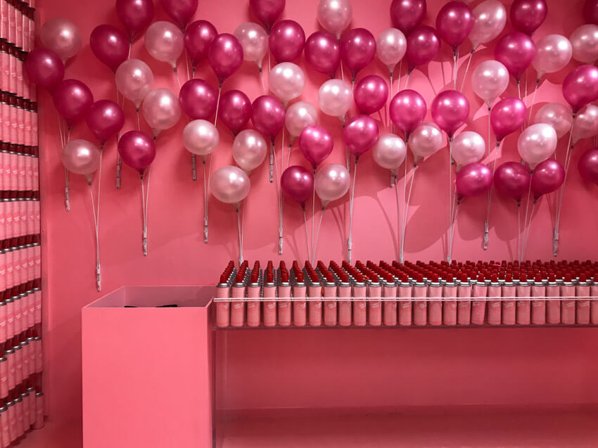 A pink painted room with a table full of pink aerosol cans. There are pink balloons attached to the wall.