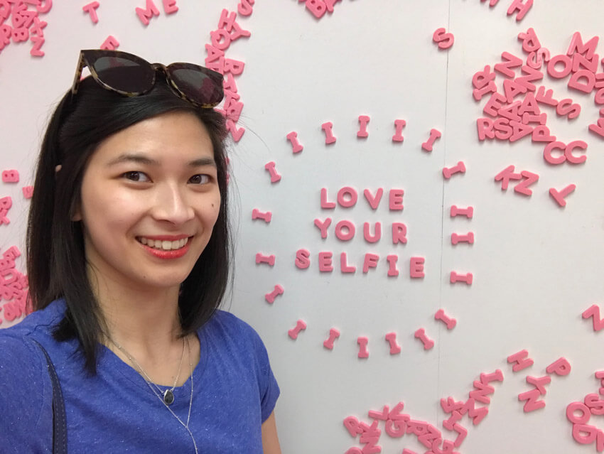 "A woman with short dark hair in a blue shirt, smiling. Behind her is a whiteboard reading ""love your selfie"" in pink magnetic letters"