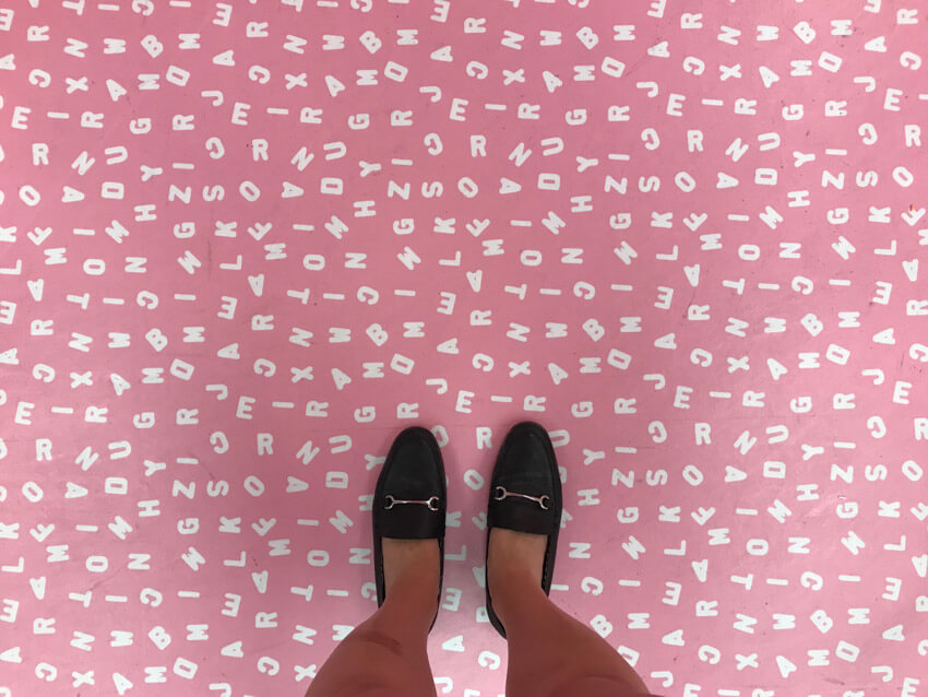 A light pink floor with a pattern of white uppercase letters. A woman's feet wearing black loafers are at the edge of the photo.