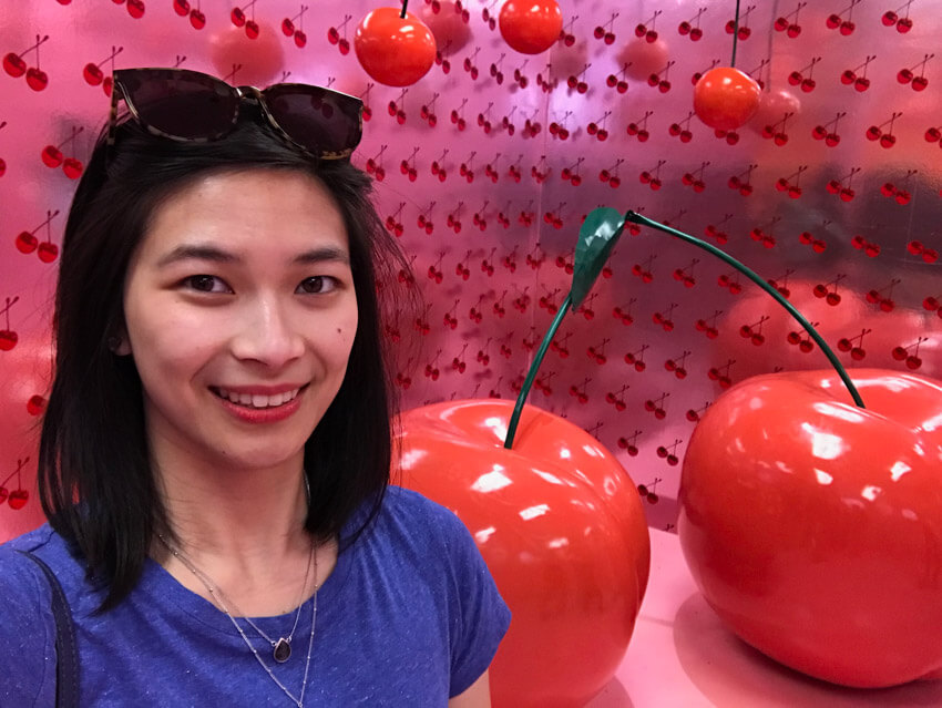 A woman with short dark hair in a blue t-shirt. Behind her is a big sculpture of two giant cherries. She is in a room with pink wallpaper with a cherry pattern.