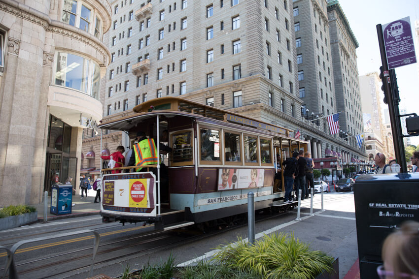 A cable car on a street with high-rise hotels in the background. Some people are standing and hanging onto the platforms at the side of the cable car.