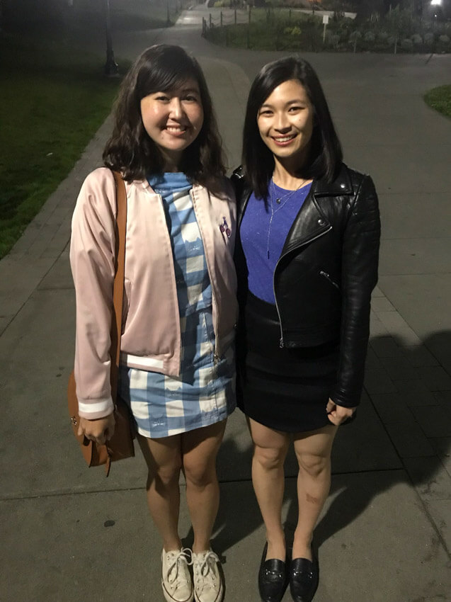 Two women joined at the hip, both have shoulder-length dark hair. One woman is wearing a blue and white dress with a pink bomber jacket; the other is wearing a blue shirt and a black skirt with a black leather jacket. It is evening and the women are standing in a park with a lamppost just behind them.