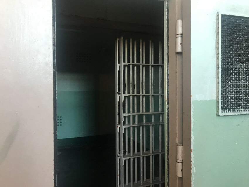The door to a very dark jail cell with no light source apart from the entrance.