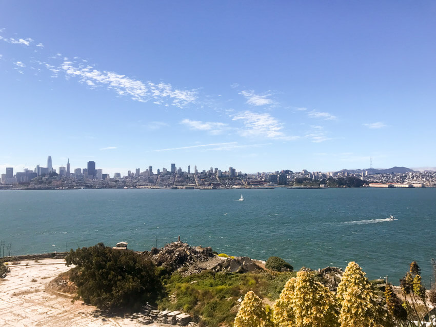 A view from an island cliff face to the sea and the city of San Francisco opposite. There are a couple of boats on the water, leaving small trails of wake.