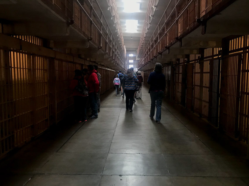A corridor of jail cells with barred entrances. A bit of light flows in from the ceiling.