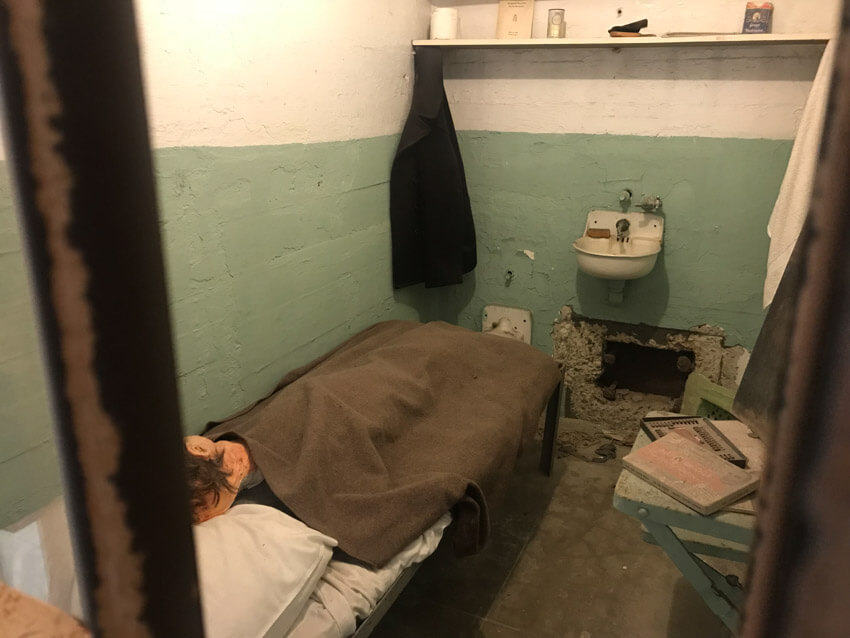 A jail cell with a model of a human head in the bed. In the wall is a small hole.