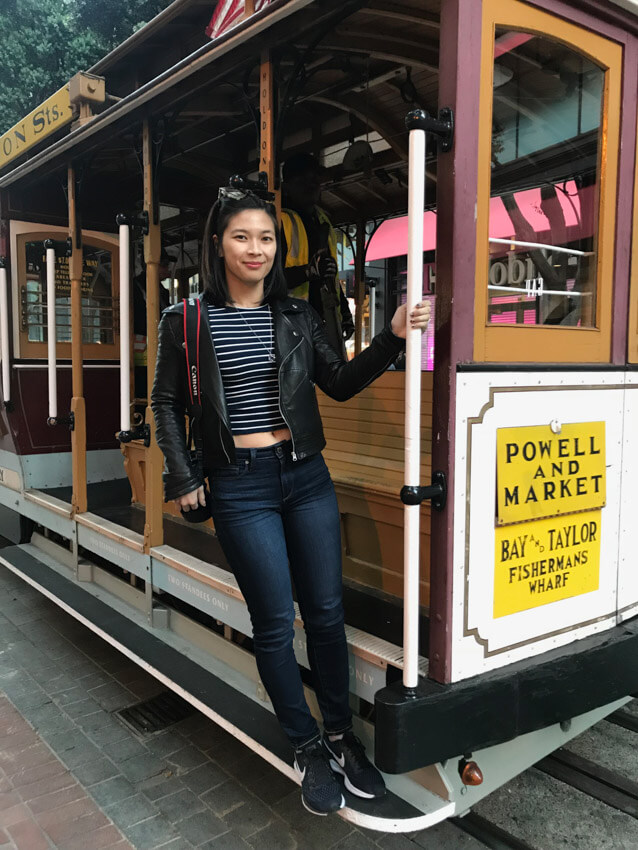 A woman in dark jeans and a striped top and leather jacket, holding onto the side of a cable car