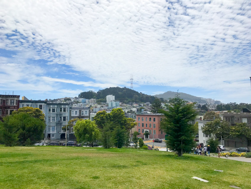 Part of the city of San Francisco, seen from the top of a green, grassy hill. In the distance, a lot of trees on a hill can be seen, as well as a communications tower. The sky is blue but filled with many scattered white clouds.