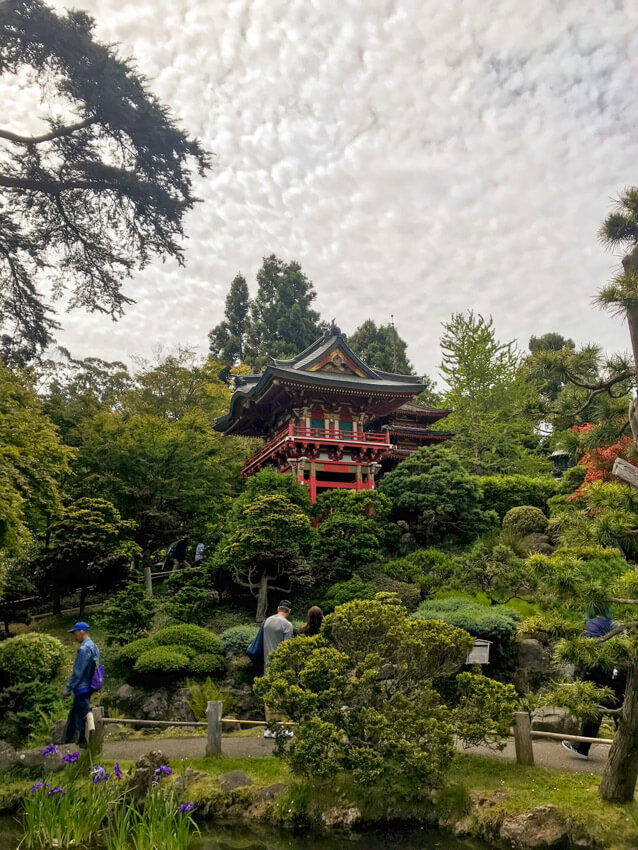 A Japanese garden full of green trees, with a Japanese-style temple house in the middle of the frame. The sky is full of white-grey clouds.