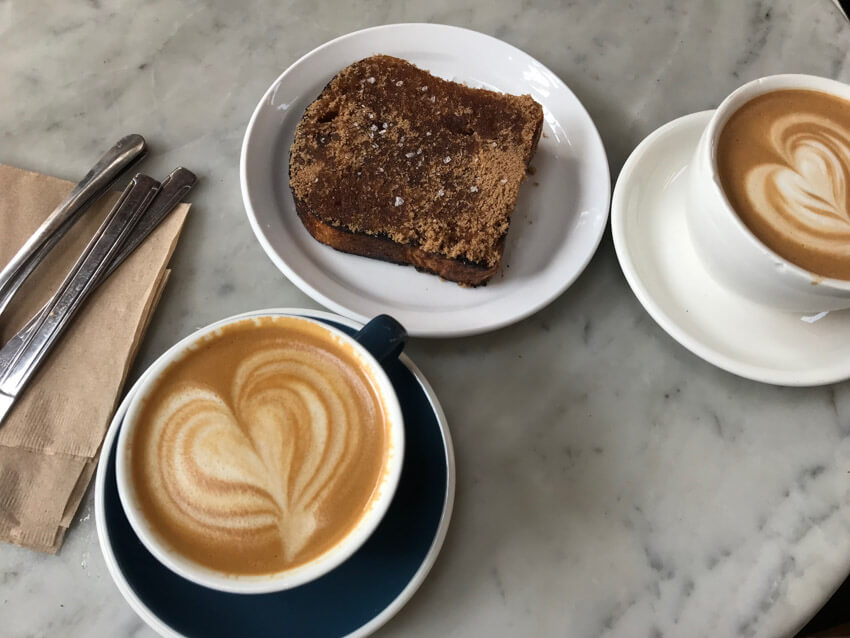 Two cups of coffee with heart-shaped coffee art, sitting on a marble surface, along with another plate of thick toast.