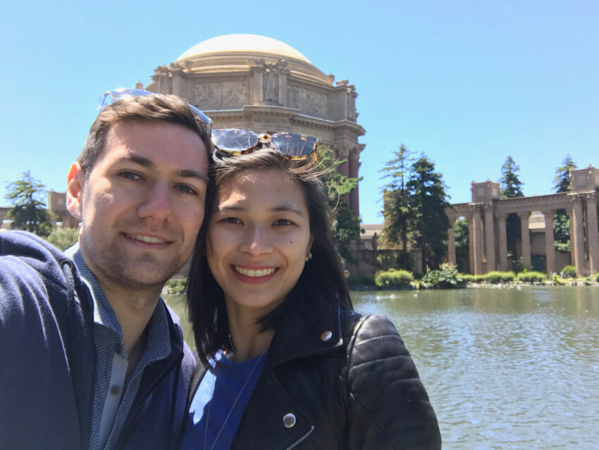 A man and woman smiling, in front of a lake with an old dome-shaped building on the other side of the lake.