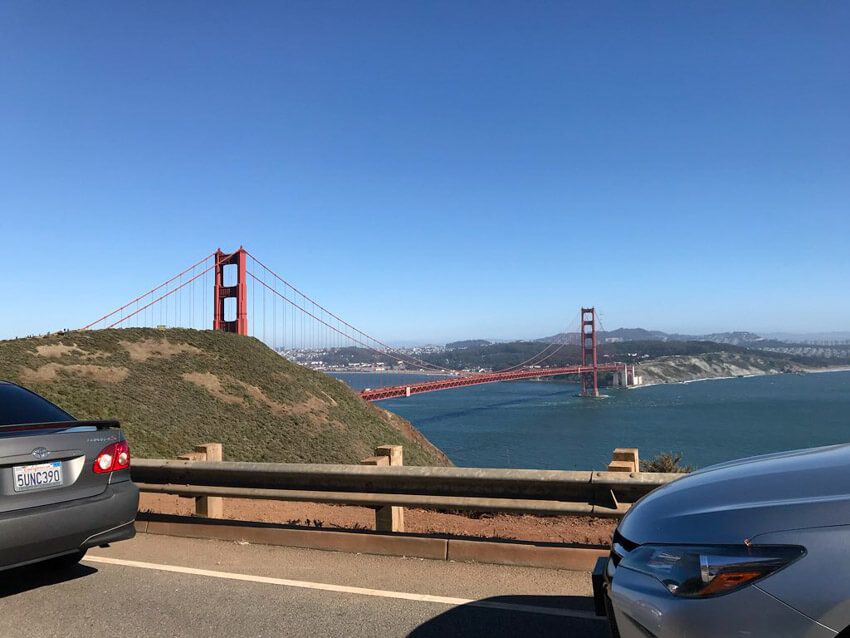 The Golden Gate Bridge in San Francisco as seen from a road at a higher altitude. The sky is very blue and it's a clear afternoon.