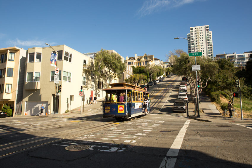 A cable car at an intersection, at the foot of a hill. It's afternoon and the foreground has a fair bit of shade while the sky is blue.