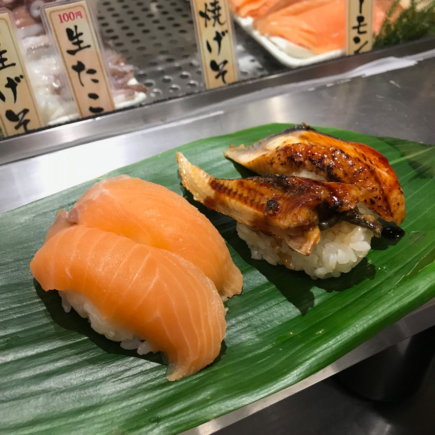 Four pieces of nigiri sushi on a large green leaf. Two are raw salmon, orange in colour, and the other two are grilled eel.