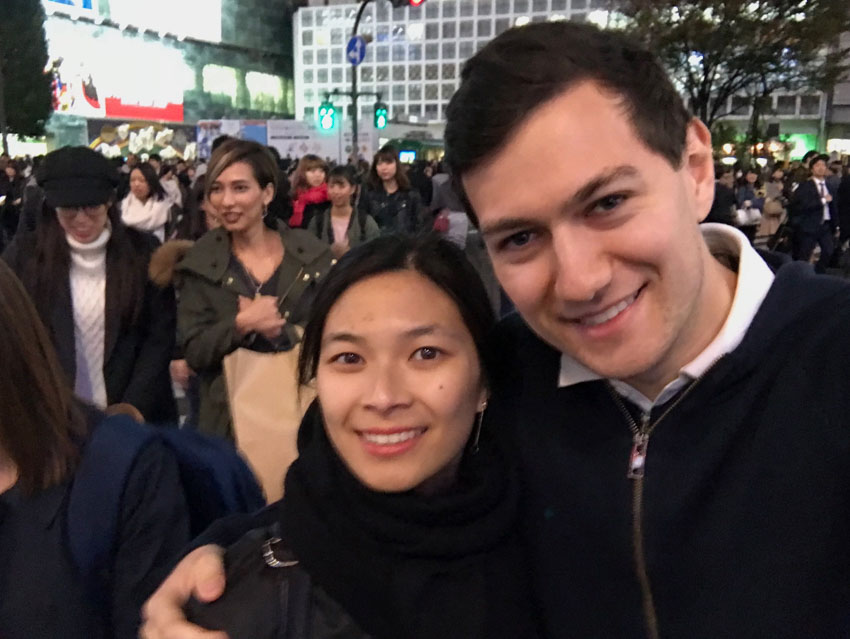 A boy and a girl smiling, wearing dark clothes. In the background are a lot of people walking.