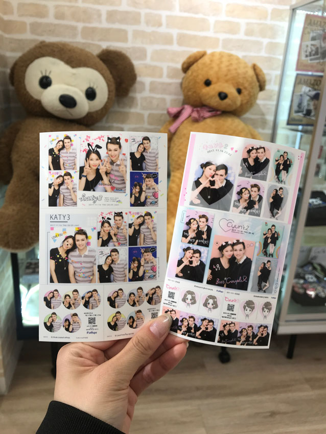 A hand holding two sheets with two sets of photos with a young couple (a boy and girl) smiling. Some of the photos are decorated with animal ears and colourful backgrounds. In the background is a big brown teddy bear and a big golden brown teddy bear.