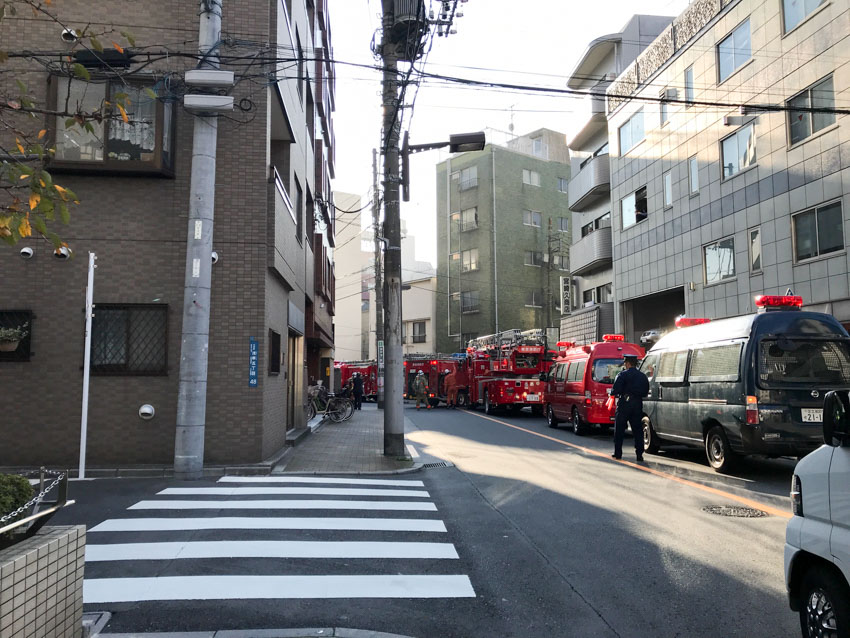 A street view with a street leading to the left, and a pedestrian crossing. There are a lot of red fire trucks in a line up the street. A police officer can be seen standing on the road.