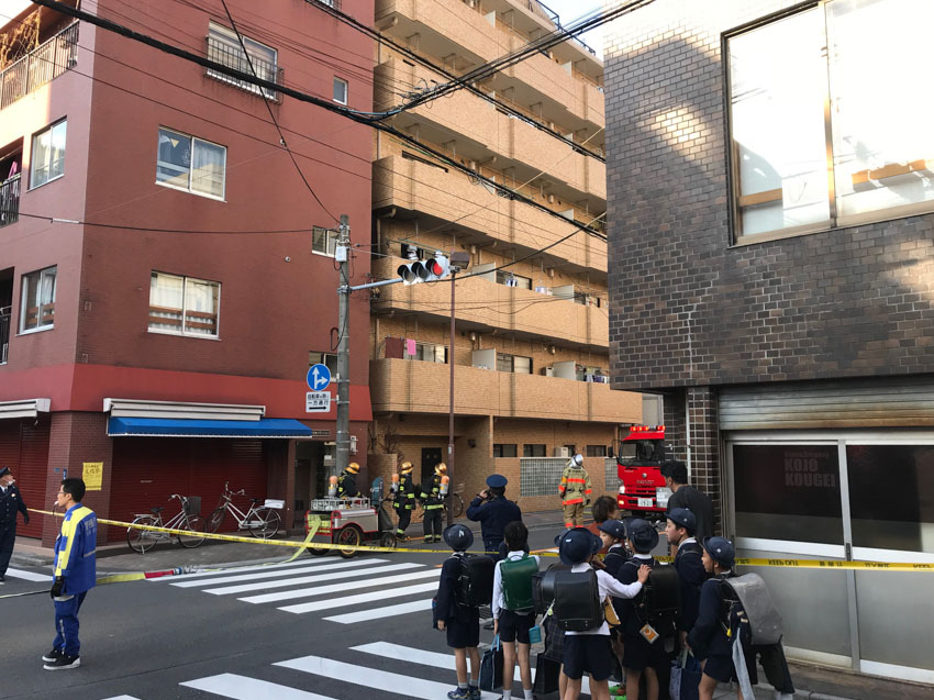 Apartment buildings at a residential intersection with access to one street blocked off by yellow tape. A small group of schoolkids are in front of the tape. Firefighters stand behind the tape, looking up at the second storey of an apartment building. The front of fire truck can be seen inside the street that is blocked off.