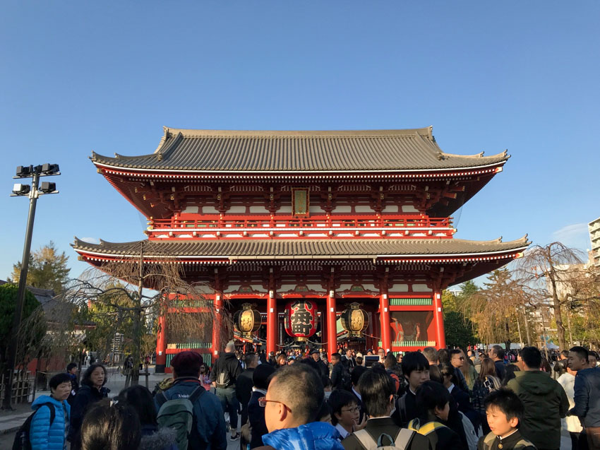 A Japanese temple with crowds of people in front of it, on a day when the sky is clear.