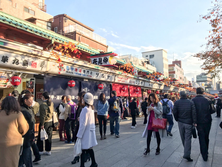 A street of shops, many of which have signage in Japanese, and red lanterns hanging from above their shop entrances. Some people walk down the path in front of the shops.