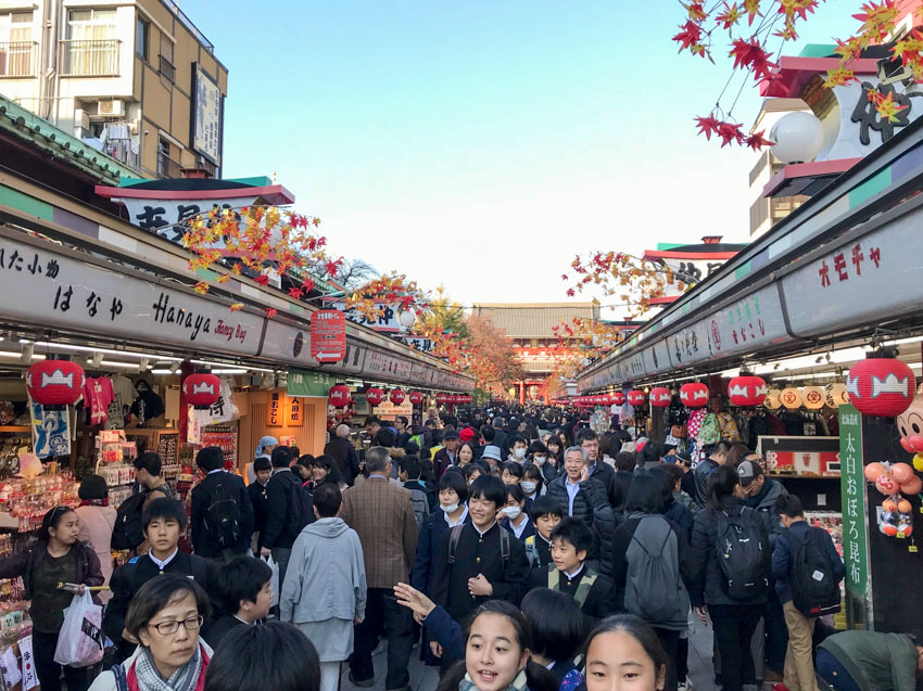 A street full of schoolchildren and people, with shops lining the sides. The shops have Japanese signage above them.