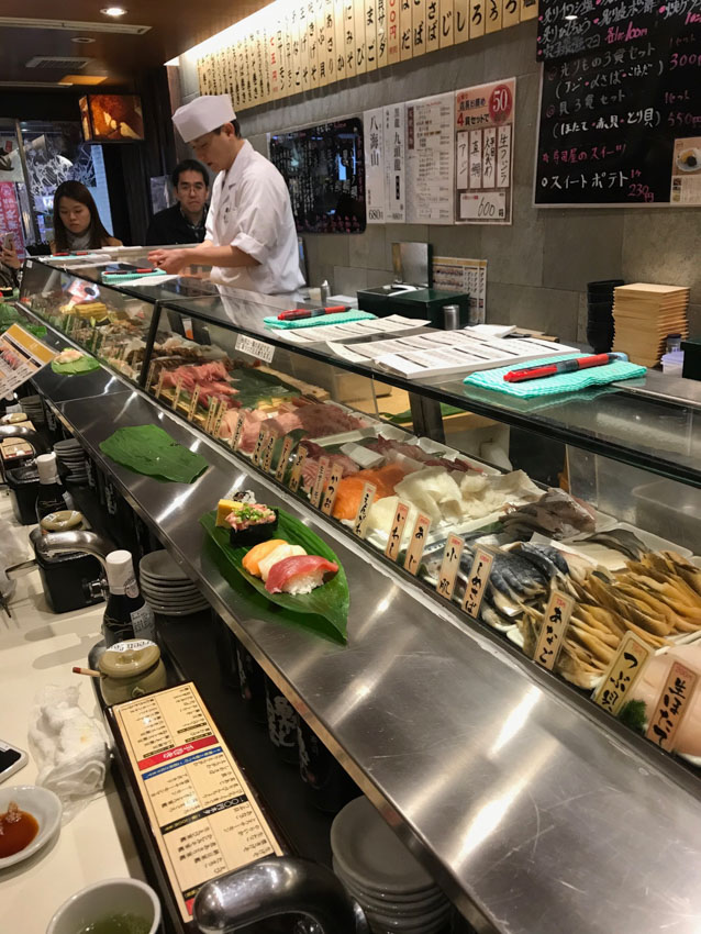 An angled side view of a standing sushi bar. There is a chef behind the counter dressed in white, some sheets of paper and pens on the glass counter, and various raw fish in the glass counter display. There are some condiments and sauces on the opposite side of the glass counter.