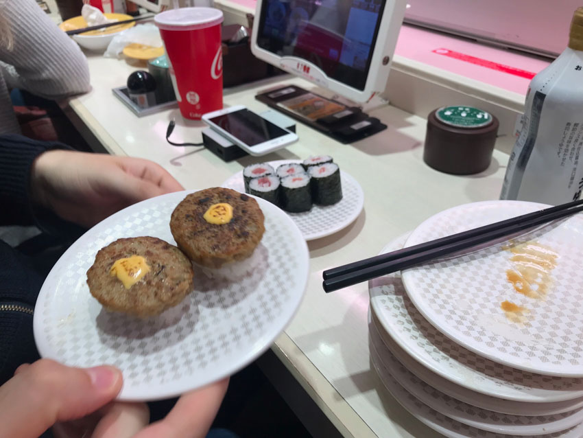 Close up view of someone holding a small white plate with a subtle textured checkered pattern, with two pieces of nigiri sushi, topped with small beef patties and yellow sauce. In the background is a sushi bar setting, with a computer screen, another plate of six maki rolls, and a small stack of empty plates in the same pattern.