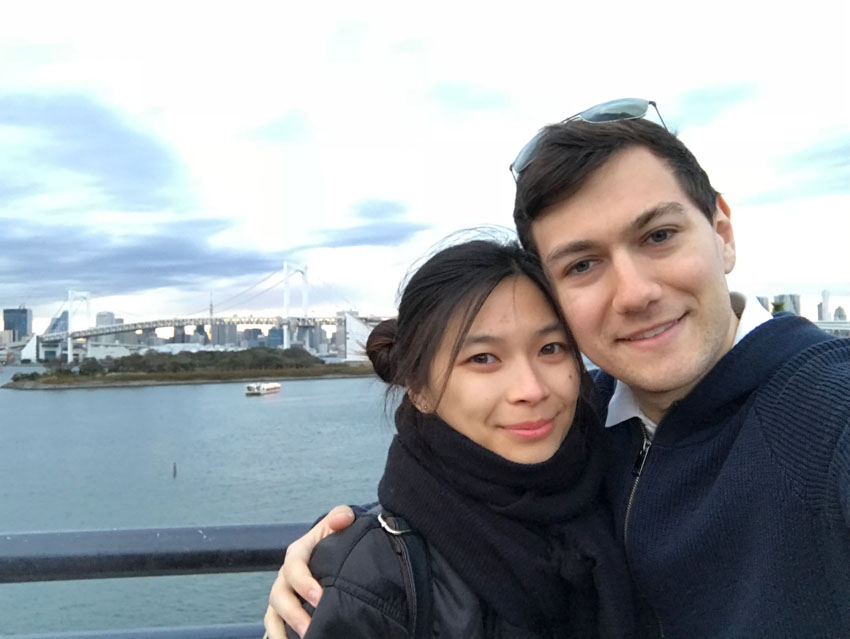 A girl and boy, smiling. They are both wearing dark clothes. The girl has a big black scarf around her neck. The boy has sunglasses on top of his head and his arm around the girl. In the background is a view of a skyline on the water, and a bridge.