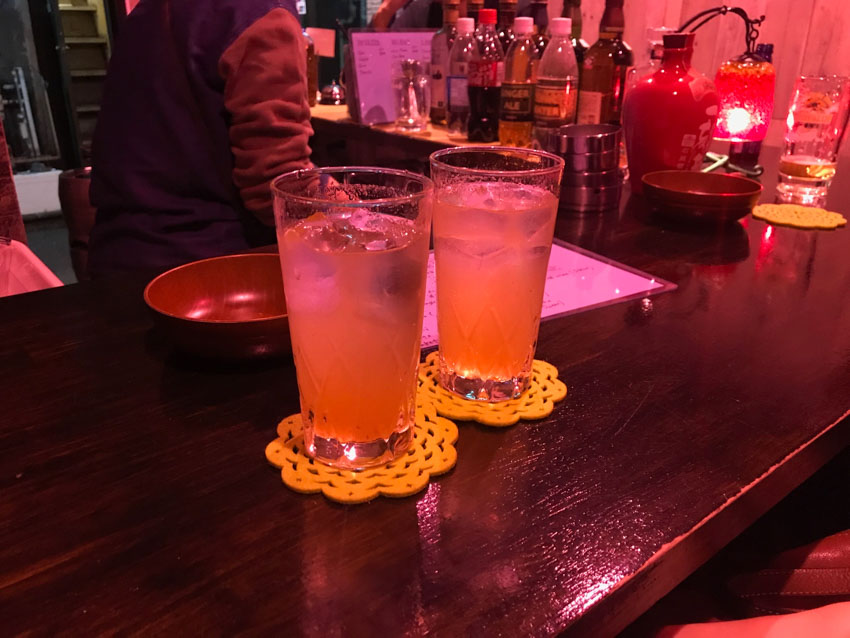 Two glasses of umeshu plum wine and soda on yellow flower-shaped coasters, sitting on a wooden tabletop in a dimly lit bar